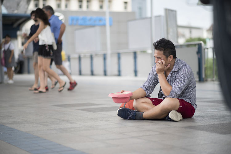 Man begging while sitting on footpath in city