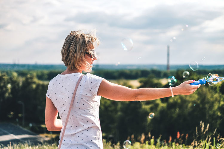 Rear view of woman blowing bubbles outdoors