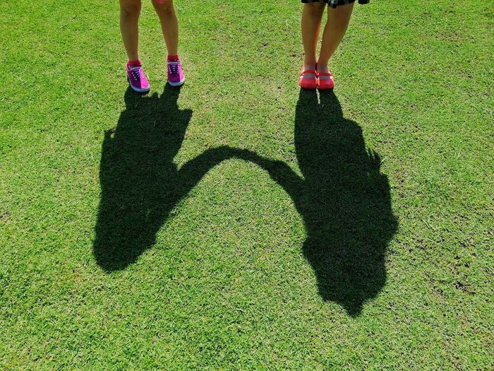 Low section of girls standing by shadow on grassy land