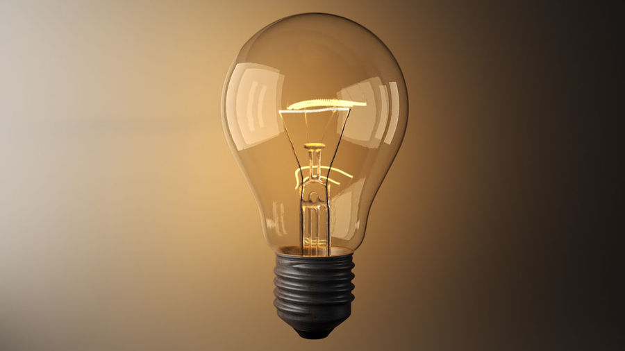 Close-Up Of Illuminated Light Bulb Levitating Against Wall