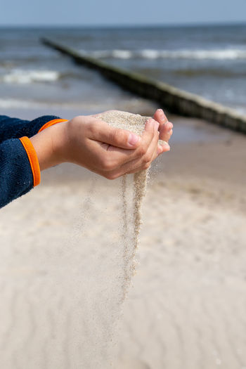 Midsection of person hand on sand at beach
