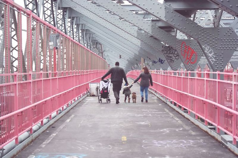 Rear View Of Family Walking On Elevated Walkway
