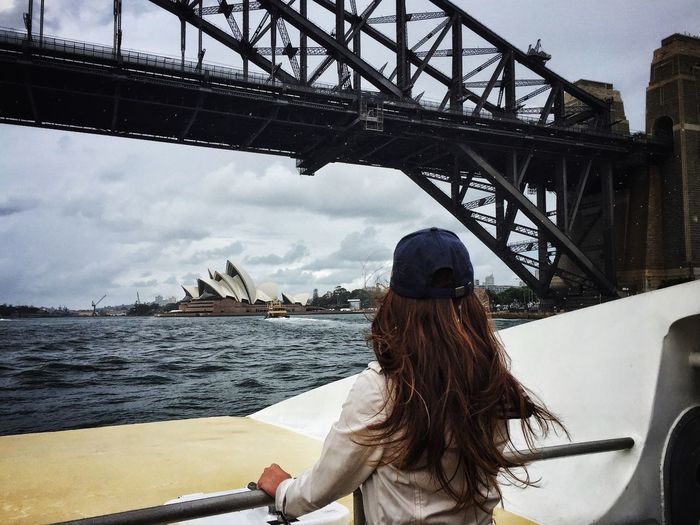 Rear View Of Woman In Boat Below Sydney Harbor Bridge Against Sky