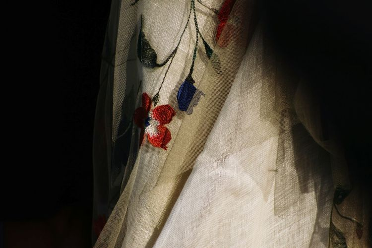 Close-up of red fabric hanging on curtain