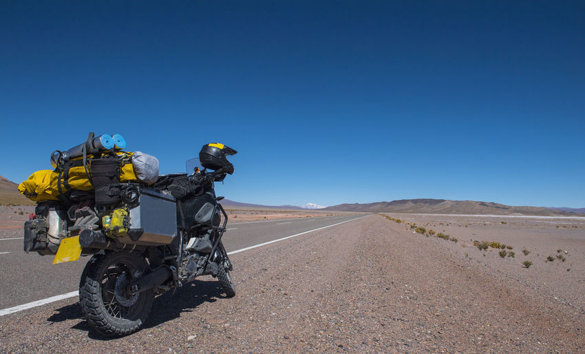 Motorcycle on road against clear blue sky