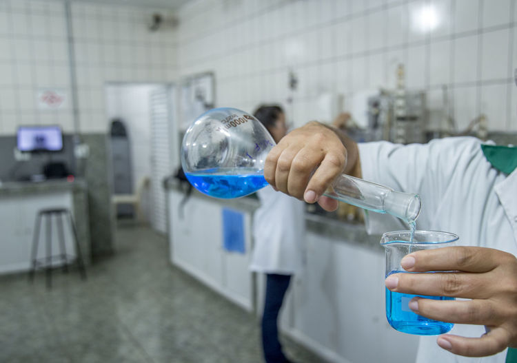 Midsection Of Scientist Pouring Liquid In Beaker At Laboratory