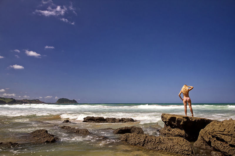 Woman standing on rock at beach against blue sky