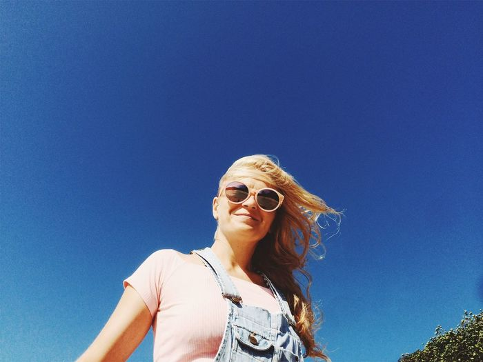 Low angle view of young woman against clear blue sky
