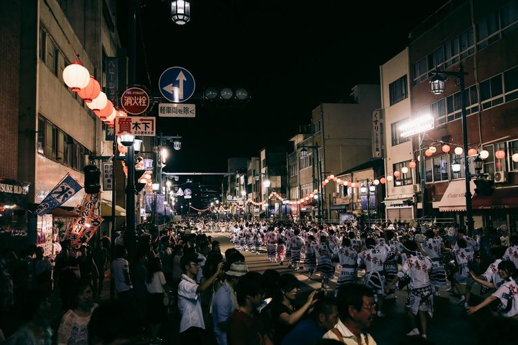 People celebrating awa odori festival on street at night
