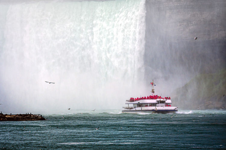 Tour boat in the mist under horseshoe falls on the niagara river