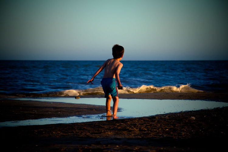 Rear View Full Length Of Shirtless Boy Standing At Beach