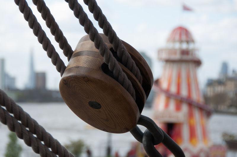 Close-up of rope against bridge in city