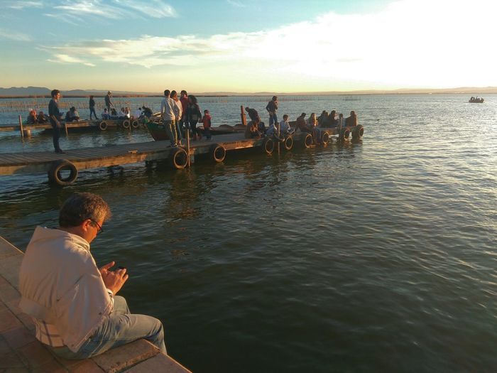 People Sitting On Pier Over Sea During Sunset