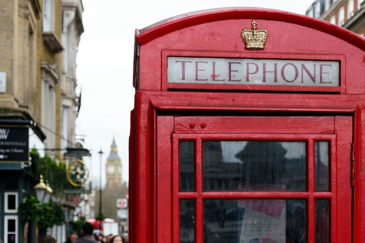 Text on red telephone booth in city