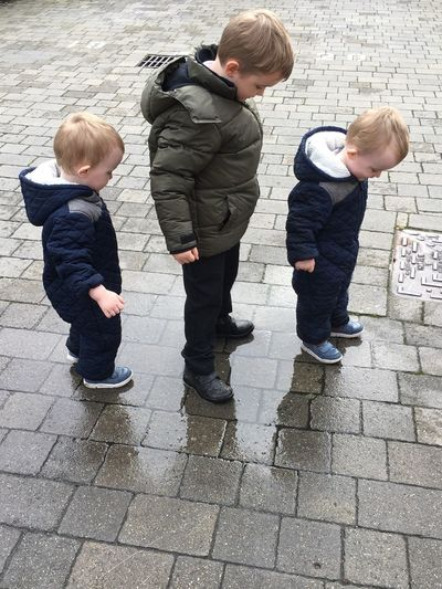 High angle view of siblings standing on footpath during rainy season