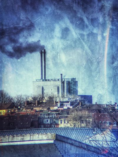 Smoke stacks in city against sky