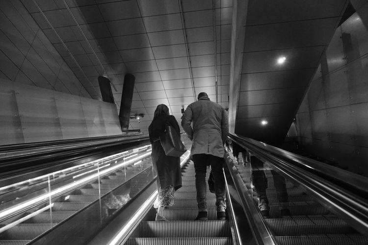 Rear view of people walking on escalator