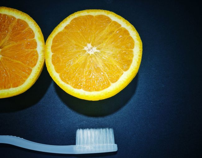 Lifestyle Natural Vitamins Fruit Sweet Healthcare Orange White Healthy Lifestyle Toothbrush Natural Food Fruit SLICE Citrus Fruit Cross Section Food Food And Drink No People Black Background Studio Shot Indoors  Freshness Close-up Day Sour Taste