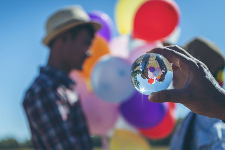 Close-up of hand holding colorful balloons