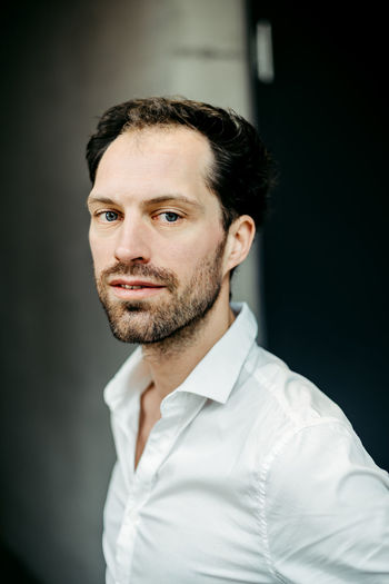 portrait of caucasian man One Person Portrait Beard Indoors  Looking At Camera Front View Facial Hair Adult Button Down Shirt Confidence  Males  Headshot Mid Adult Standing Business Person Men Focus On Foreground Contemplation Black Background Caucasian Job Handsome Confidence