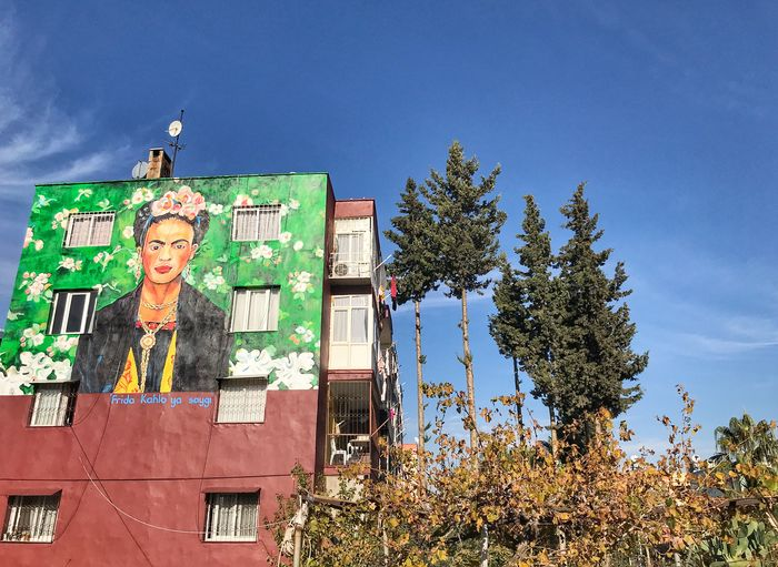 An Artwork Is Drawn On The Wall Of A Building In Mersin Province Of Turkey On December 4, 2017. Artworks Of World Famous Artists; Like Vincent Van Gogh, Osman Hamdi Bey, Pablo Picasso Or Salvador Dali Are Drawn On The Walls Of Buildings At A Boulevard, By Human Representation Male Likeness Statue Tree Architecture No People Low Angle View Sculpture Built Structure Building Exterior King - Royal Person Window Box Residential Building Palm Tree City Cloud - Sky Nature Low Angle View House