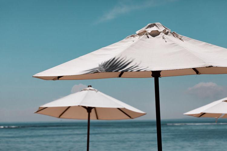 Umbrellas on beach by sea against sky