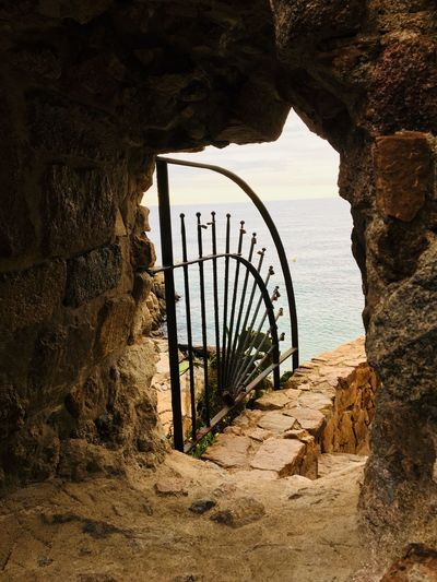 View of gate on rock formation against sea