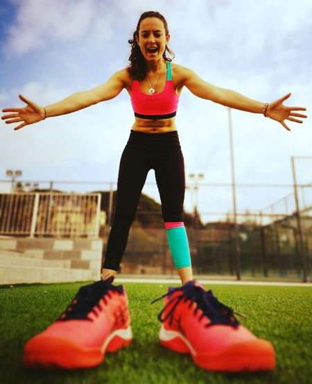 Low Angle View Of Woman With Arms Outstretched Wearing Large Shoes On Field