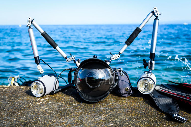 Professional underwater photography equipment for DSLR camera with strobes. Wide angle dome for fish-eye dual flashes with arms in aluminium casing on a pier with blue sea in the background. Camera DSLR Photographic Equipment Slovenia Travel Casing Day Equipement Nature No People Outdoors Photographer Piran Sea Strobes Submarine Underwater Underwater Camera Underwater Case Underwater Photography Vacation Water