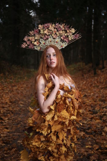 Thoughtful young woman wearing flowers on hair standing at forest during autumn