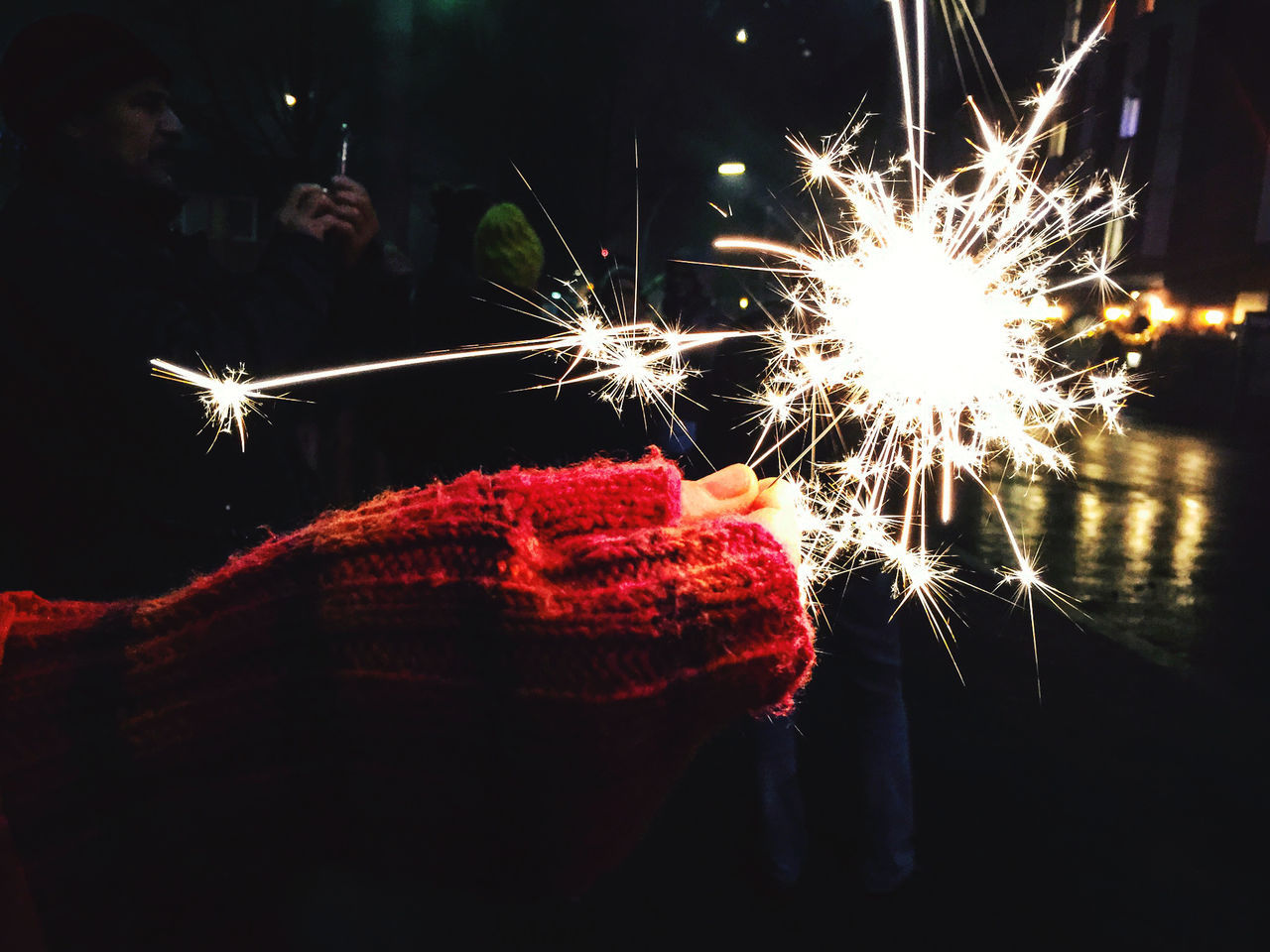 Cropped hand wearing sweater holding sparklers on street