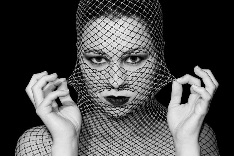 Close-Up Portrait Of Woman Wearing Lipstick And Netting Against Black Background