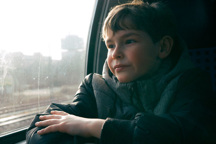 Boy looking through window while traveling in train