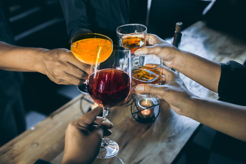 Group of happy friends drinking and toasting alcohol. Drink Alcohol Refreshment Glass Human Hand Food And Drink Hand Real People Men Holding Wine Human Body Part Wineglass Lifestyles Group Of People Togetherness Red Wine Friendship Midsection People Celebratory Toast