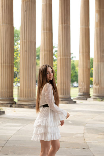 Portrait of young woman standing against columns