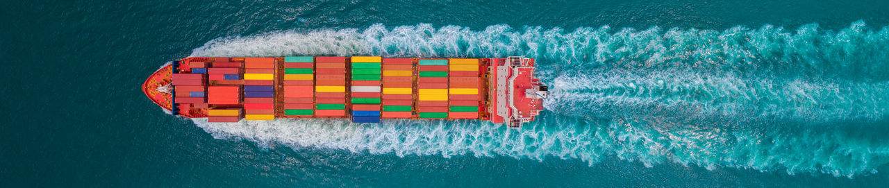 Aerial top view of cargo ship with contrail in the ocean sea ship carrying container and running