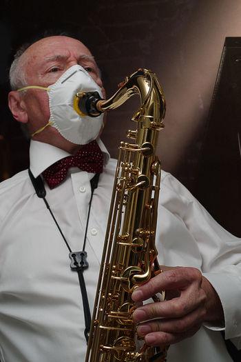 Senior man wearing mask playing saxophone