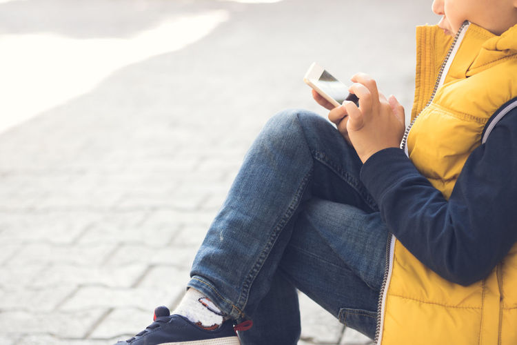 Midsection of boy using mobile phone on street