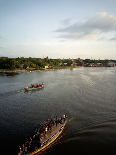 High angle view of people on boat in river against sky