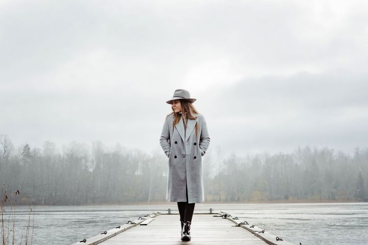 Woman standing by lake against sky during winter