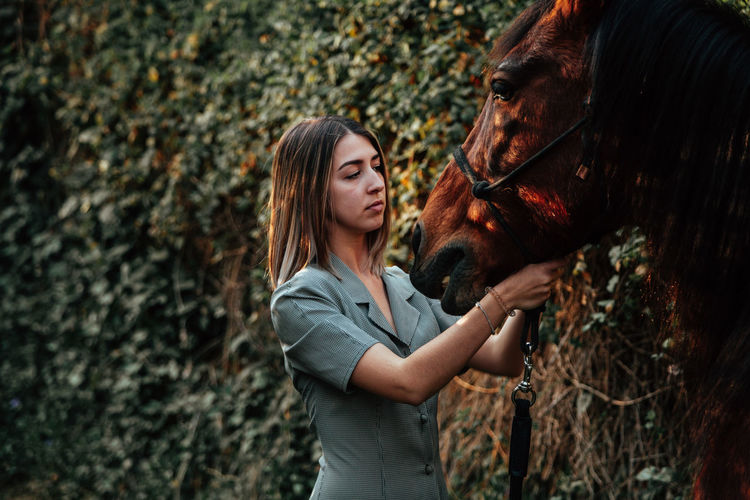 Close-up of young woman standing with horse outdoors