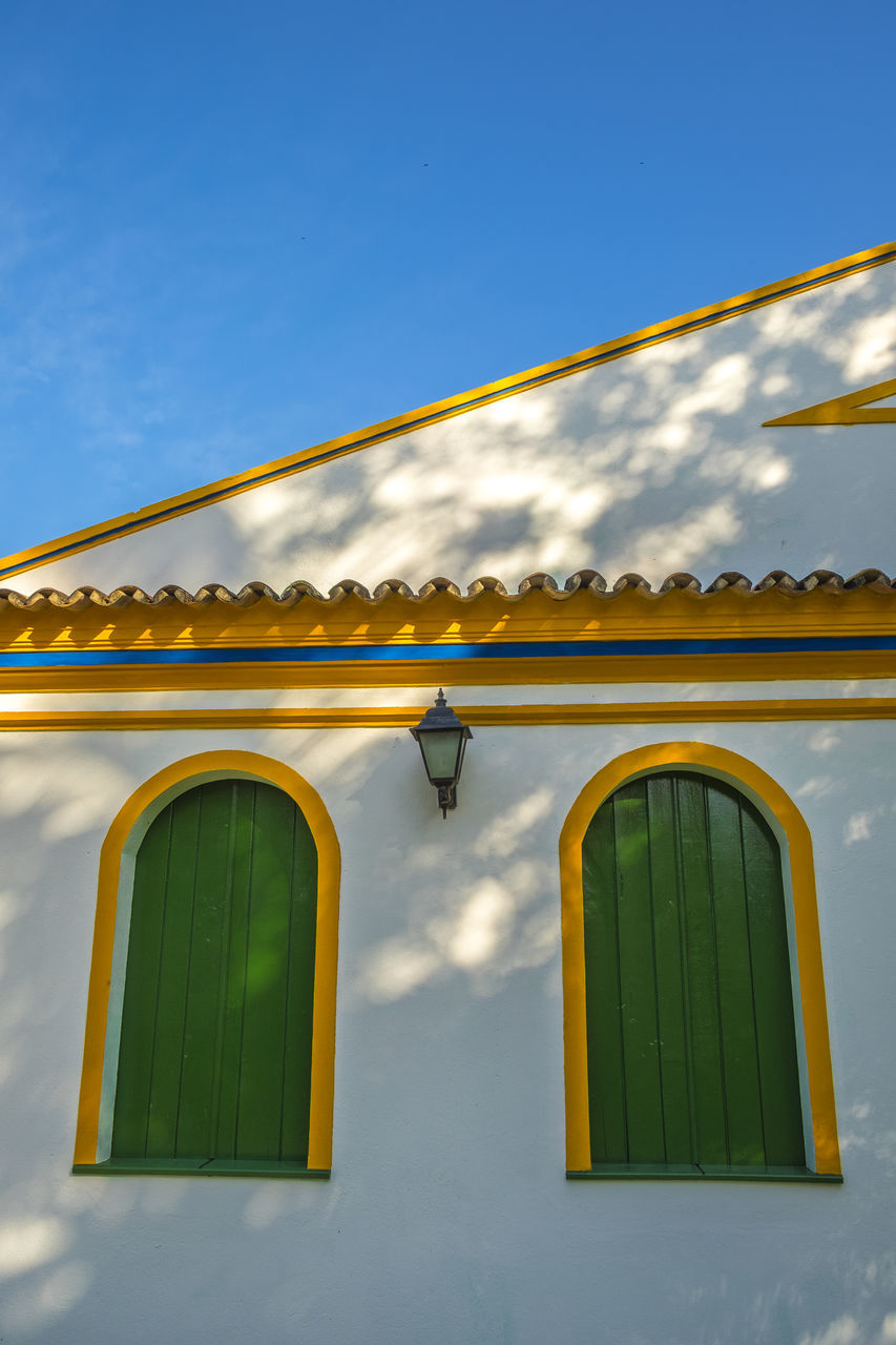 yellow, green color, built structure, architecture, day, outdoors, low angle view, sky, sunlight, no people, building exterior, nature
