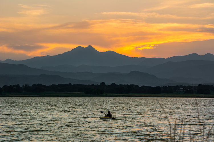 Silhouette Man Kayaking On River Against Mountains During Sunset