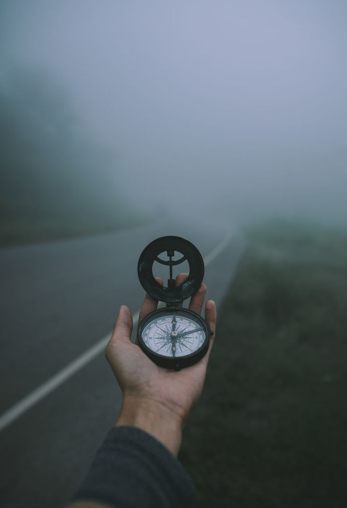 Close-up of hand holding navigational compass on road during foggy weather