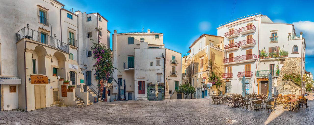 Buildings in city against blue sky