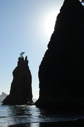 Silhouette rock formation in sea against clear sky