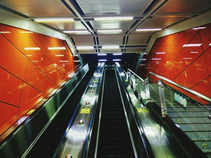 Low angle view of illuminated escalators at subway station