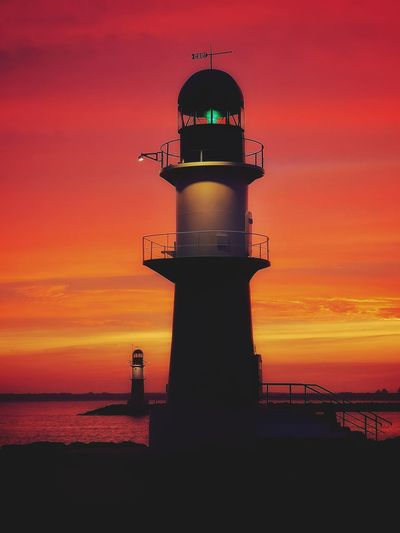 Lighthouse against sea during sunset