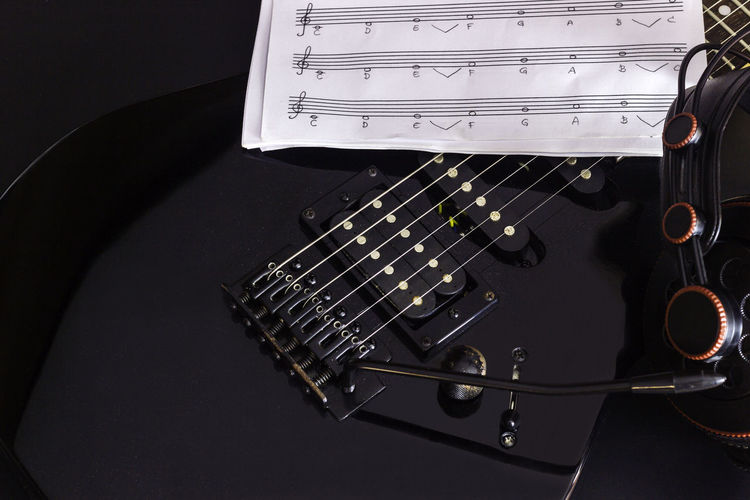 Close-Up Of Guitar And Sheet Music Against Black Background
