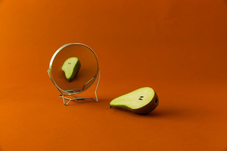 Vanity fruit Pear Fruit Minimal Simple Minimalism Mirror Vanity Fruit Healthy Eating Food Food And Drink Still Life Indoors  Wellbeing Studio Shot Colored Background Freshness Yellow Green Color Close-up Orange Color Table SLICE